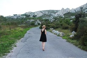 girl in black dress on Mountain Road, back view