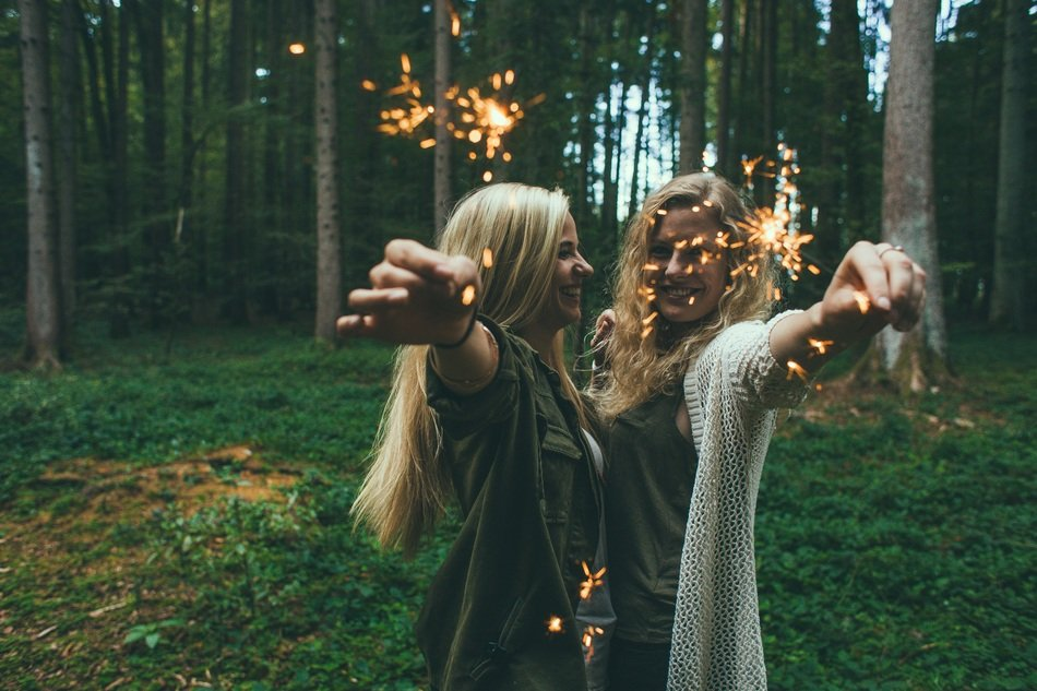 two joyful Girls with Sparklers in hands in forest