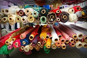 rolled up multi-colored fabrics on a market counter