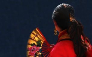 back view of asian Woman holding Red Fan