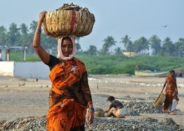 indian woman on her head with a basket full of fish