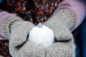 wedding ring on the snow in the hands of a girl