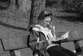black and white photo of a woman with a book on a bench