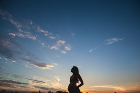 pregnant woman silhouette in the blue sky