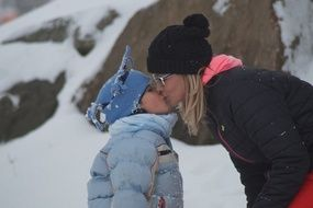 mom kisses a child outdoors in winter