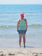 woman in a wide hat on a sunny beach