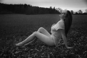 black and white photo of a topless girl in nature