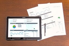 business analytics on a tablet and printed business plans