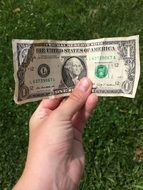 in the hands of a person 1 dollar