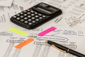 pen and calculator on accounting documents