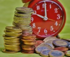 euro coins and red clock