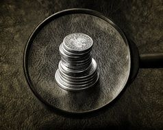 silver coins under a magnifying glass