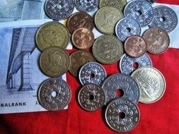coins and banknotes on red cloth