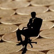 businessman in chair on the coins background