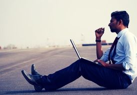 man sits on the ground with laptop
