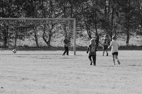 black and white photo of children playing soccer