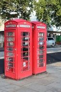 two red phone booths on the street of london