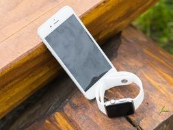 white Iphone and Iwatch on the wooden bench