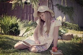 little girl reads a book in a green meadow