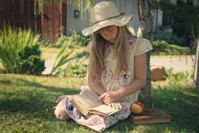 little girl is reading a book while sitting on green grass
