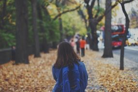 a girl with a backpack is on dry leaves