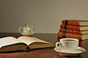 white cup with coffee and books on the table