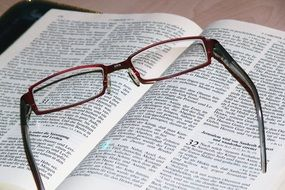 glasses lie on an open bible