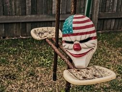 mask of a creepy clown in an abandoned yard