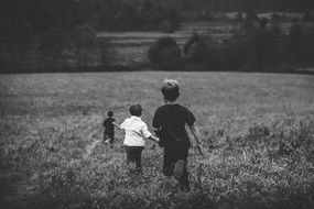 boys playing in the field in black and white
