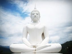 white statue of the buddha against a background of clouds
