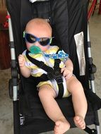 baby in sunglasses in a stroller