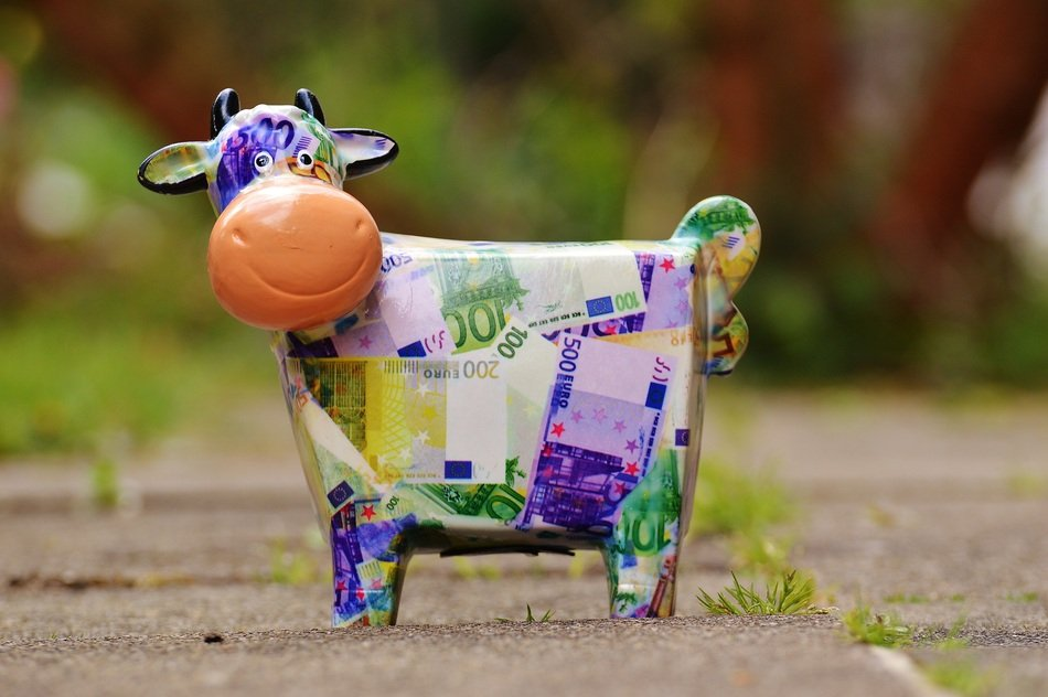 piggy bank in the shape of a multi-colored cow