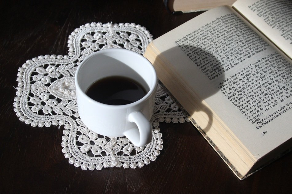 A cup of coffee near book are on the table