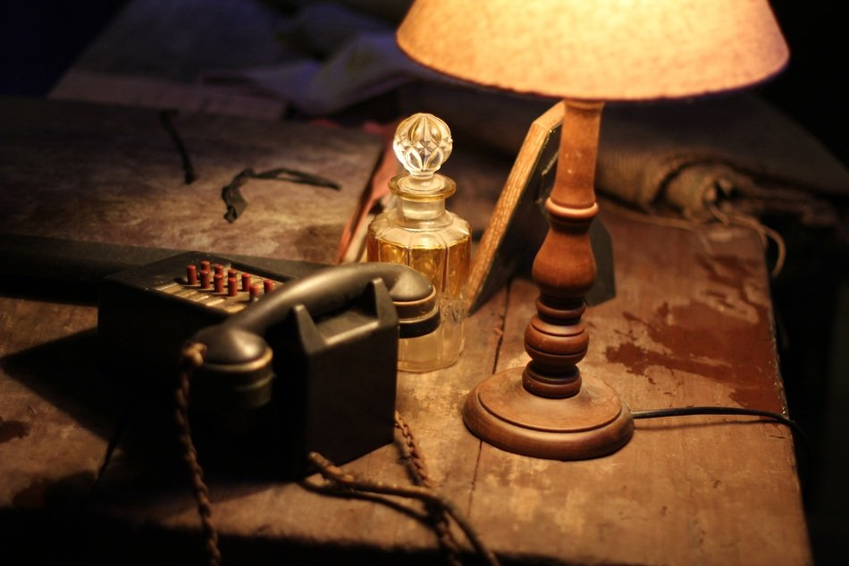 vintage table lantern, stationery phone and bottle on dirty wooden table