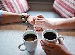hands of lovers and two cups of coffee in an Italian cafe