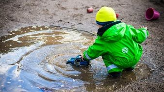 boy playing in the puddle