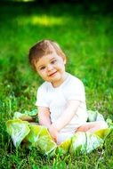 little girl sitting on green grass