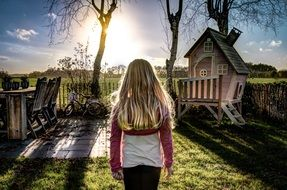 little girl stands in the sunlight