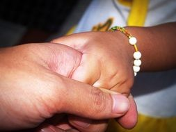 child's hand in the hands of an adult