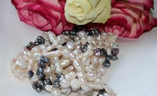 pearl necklace near a bouquet of roses