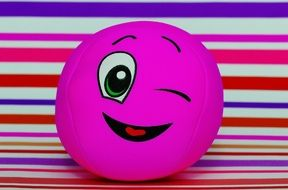 pink ball with a smile on a striped background