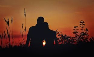 silhouette of a couple in love on sunset background