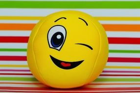 yellow ball with a winking emoticon