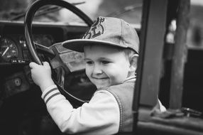 black and white photo of a child driving a car