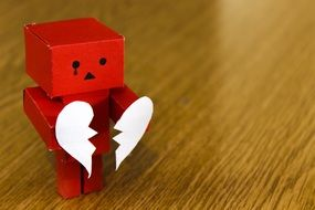 cardboard figure with a torn heart