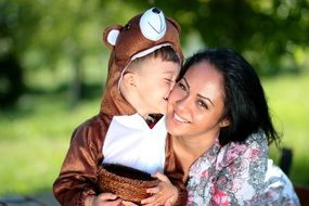 child in a bear costume kisses mom
