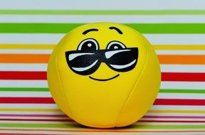 yellow ball with a playful smile in glasses