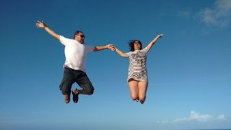 photo of a jumping couple against a blue sky