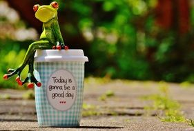 Coffee to go and frog figure