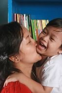 mom and son kissing and laughing